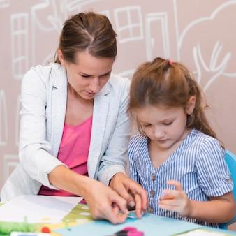 Девушка среднего кадра и учитель склеивают бумагу