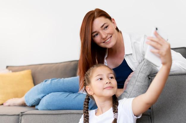 Средний снимок девушки и женщины, делающей селфи
