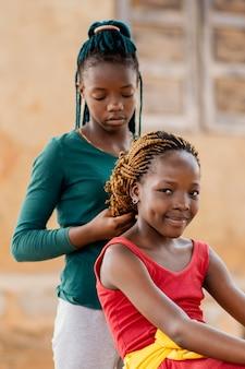 友達の髪を編むミディアムショットの女の子