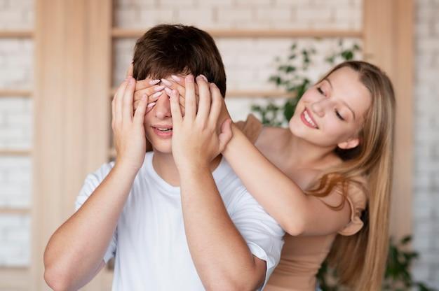 Девушка среднего кадра, закрывающая глаза мальчика