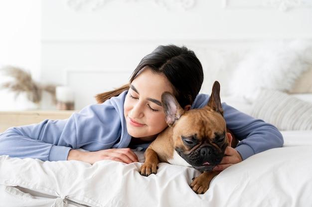 Ragazza e cane del colpo medio a letto
