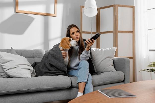 Medium shot girl and dog under blanket