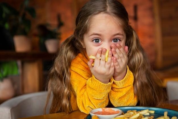 Ragazza del colpo medio che mangia patatine fritte