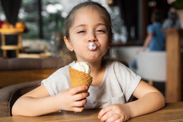 Ragazza del colpo medio che mangia il gelato