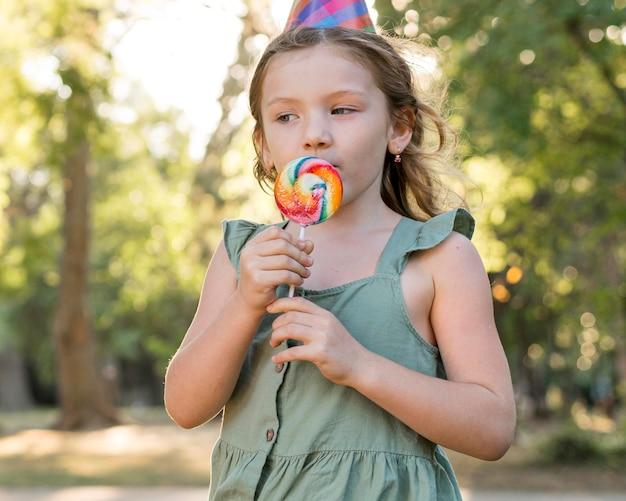 ロリポップを食べるミディアムショットの女の子