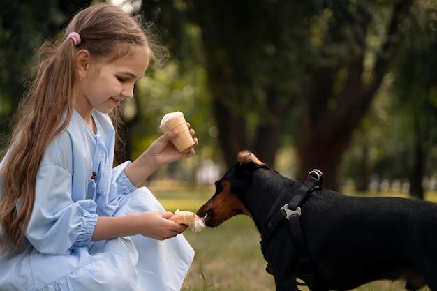 Medium shot girl feeding dog