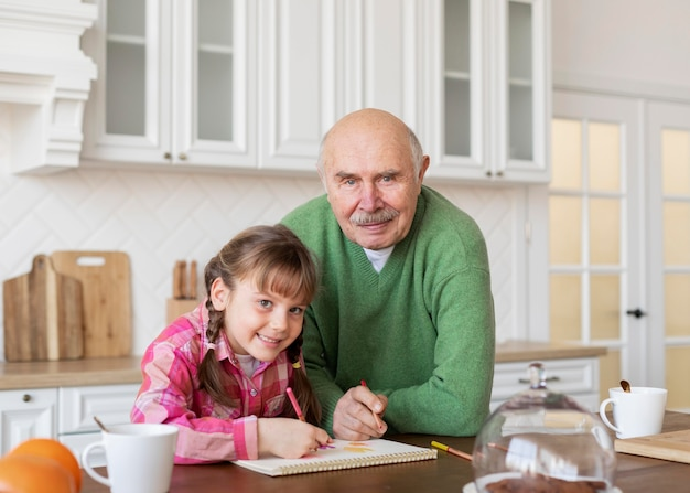 Medium shot girl and grandfather drawing