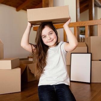 Medium shot girl holding box