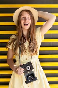 Средний снимок девушка держит камеру