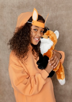 Medium shot girl holding fox toy