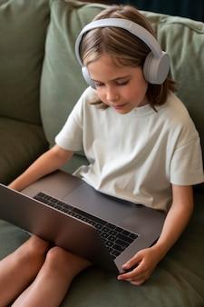 Девушка среднего выстрела, держащая ноутбук дома