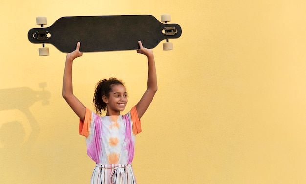 スケートボードを持っているミディアムショットの女の子