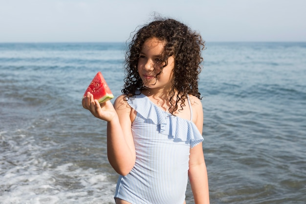 Medium shot girl holding watermelon