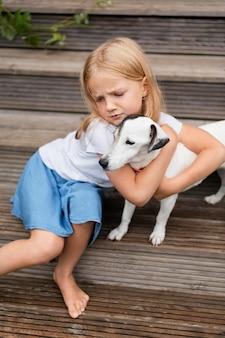Девушка среднего выстрела обнимает собаку