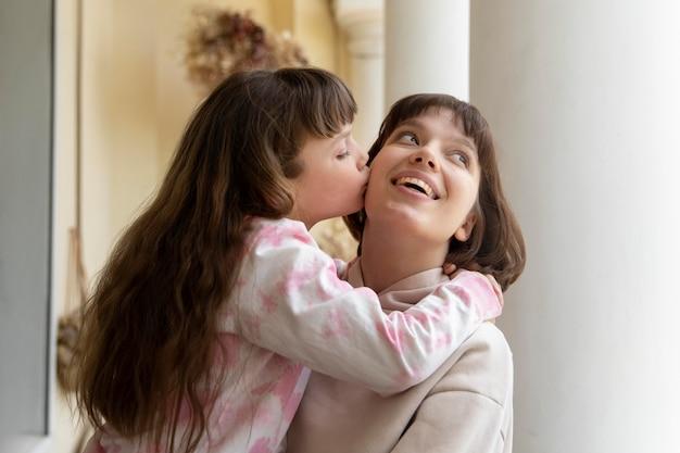 Medium shot girl kissing mother on cheek