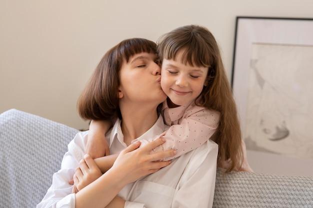 Medium shot girl kissing woman on cheek