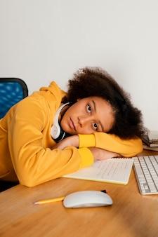 机の上に横たわるミディアムショットの女の子