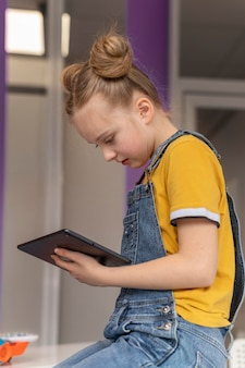 Medium shot girl learning with tablet