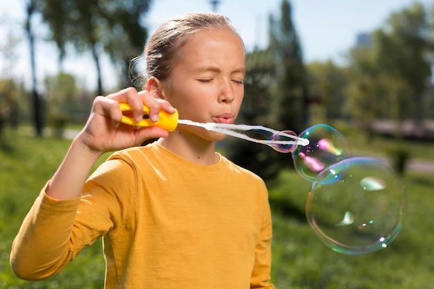 Medium shot girl making soap bubbles outside