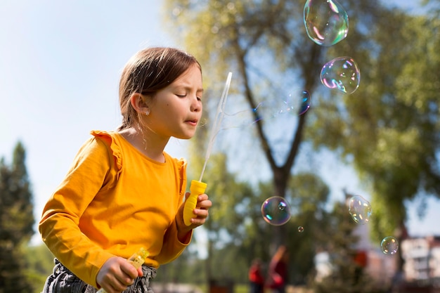 Medium shot girl making soap bubbles