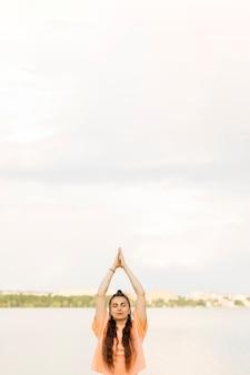 Medium shot girl meditating outdoors