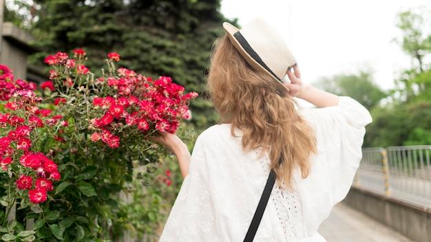 花の近くのミディアムショットの女の子