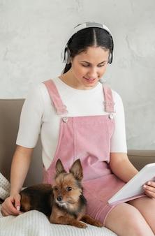 Девушка среднего выстрела на диване с планшетом и собакой