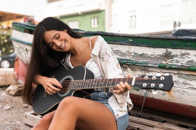 Девушка среднего кадра играет на гитаре