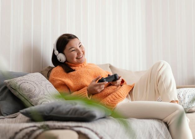 ソファでビデオゲームをしているミディアムショットの女の子