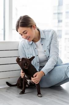 Девушка среднего выстрела играет с собакой