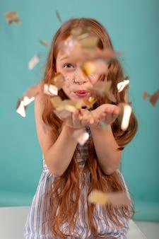 Девушка среднего кадра позирует с конфетти
