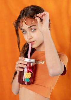 Девушка среднего выстрела позирует с напитком