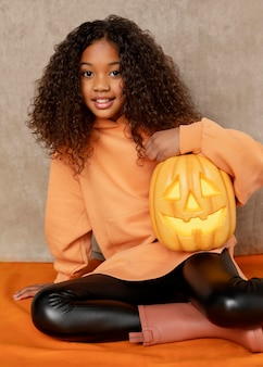 Medium shot girl posing with pumpkin