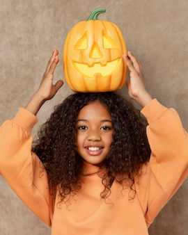 Medium shot girl posing with pumpkin