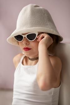 Девушка среднего кадра позирует в темных очках