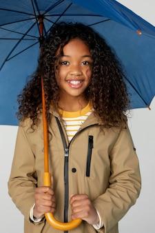 傘でポーズをとるミディアムショットの女の子