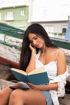 Девушка среднего кадра читает книгу на открытом воздухе