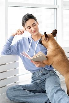 Девушка среднего кадра читает возле собаки