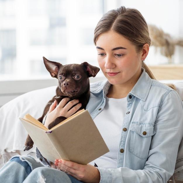 Девушка среднего кадра читает с собакой