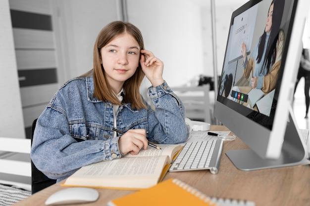 Medium shot girl sitting at desk