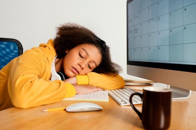 机の上で寝ているミディアムショットの女の子