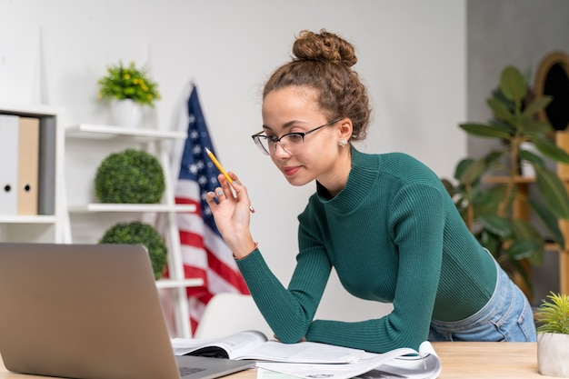 Medium shot girl studying with laptop