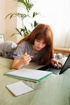 ノートパソコンで勉強しているミディアムショットの女の子