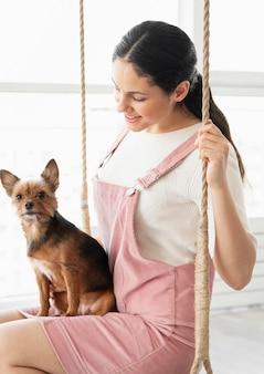 Medium shot girl on swing with dog