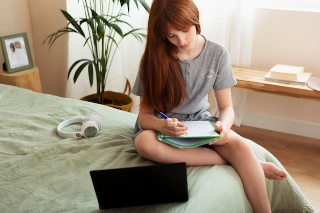 Medium shot girl taking notes in bed