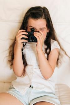 Medium shot girl taking photos with camera