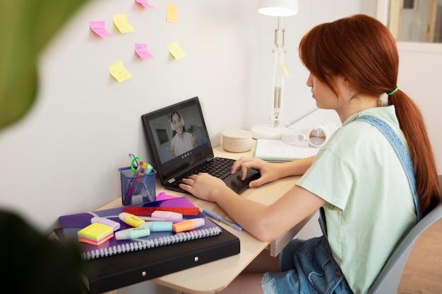 Medium shot girl typing at home