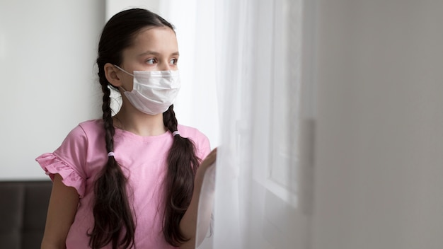 Medium shot girl wearing medical mask