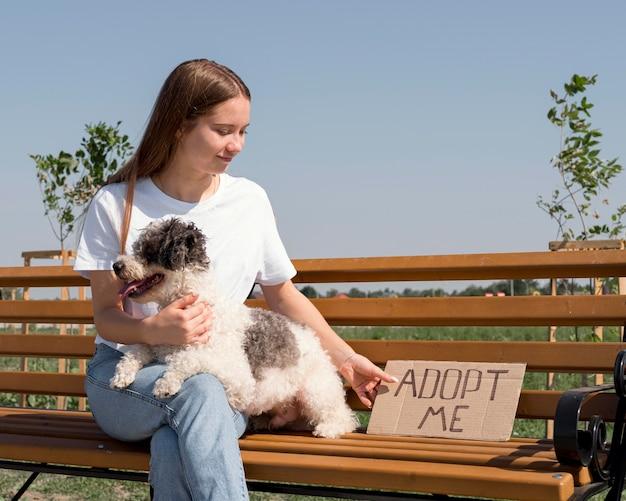 Девушка среднего выстрела с милой собакой на скамейке