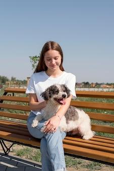 Ragazza del colpo medio con il cane sulla panchina
